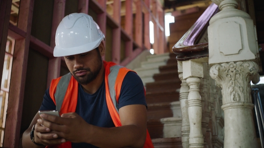 Portrait of builder on site looking at phone