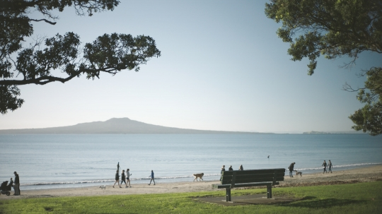 Beach scene with walkers and park bench