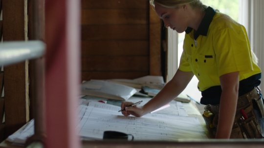 Builder looking at house plans on construction site