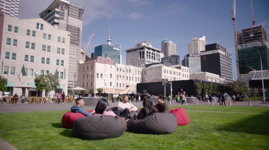 Friends sitting on beanbags in public square - stock video