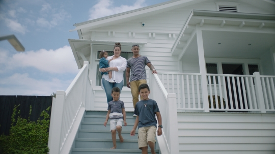 Family walk down the front steps of their new home - stock video