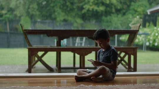 Boy plays on phone while rain falls outside - stock video