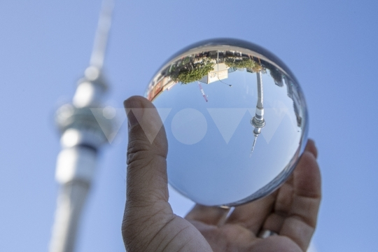Hand holding crystal ball in front of Sky Tower