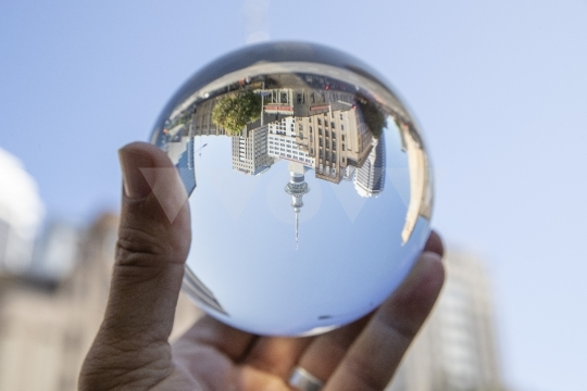 Hand holding crystal ball in urban street