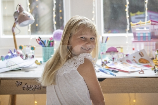 Girl at desk doing craft - stock photo
