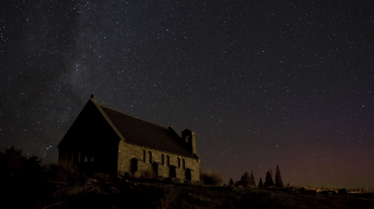 Timelapse of night sky with old church in foreground
